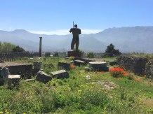 modern statue amidst ruins of Pompeii