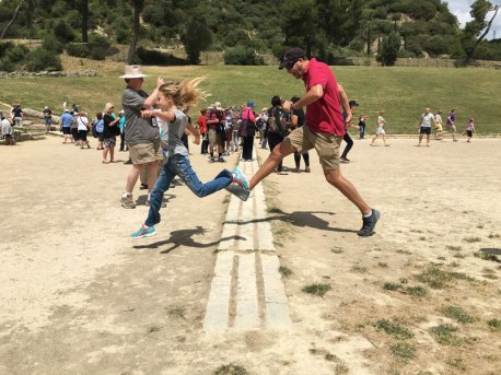 crossing the finish line in ancient Olympian stadium