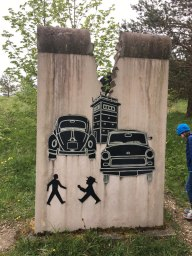 art showing West and East German cars and walk signals and watchtower