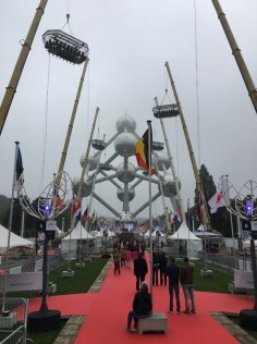 """Dinner in the Sky"" tables hoisted on cranes in front of the Atomium"